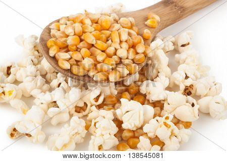 Corn seeds and popcorn with wooden spoon