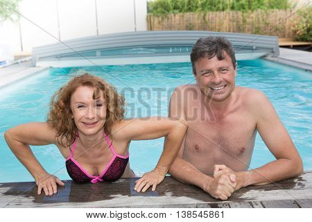 Portrait Of Happy Middle Aged Couple Relaxing On The Edge Of Swimming Pool