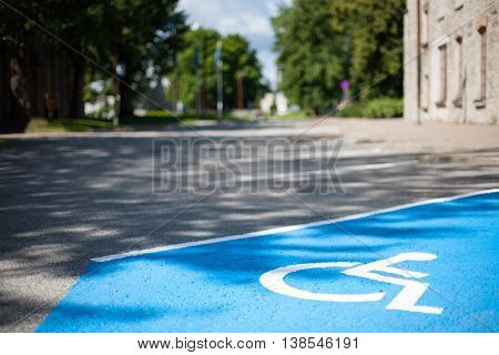 Closeup of an empty handicapped reserved parking space painted blue with a white wheelchair symbol on black asphalt in the city