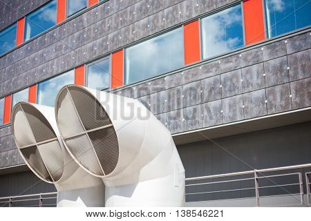 Industrial background of two big modern ventilation pipe tops in front of an office building