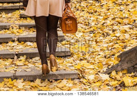 Women's Feet Are On The Stairs In The Park With Golden Autumn Leaves
