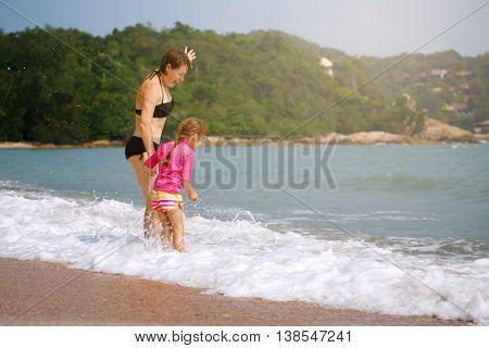 Happy family playing in blue water on a tropical resort at the sea. Summer vacations concept