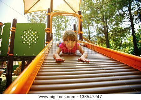 Little girl goes for a drive on a children's hill