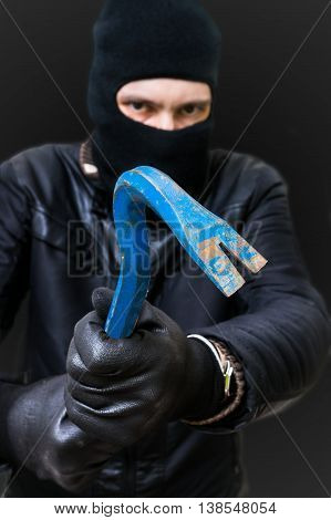 Masked burglar or thief with balaclava and crowbar.