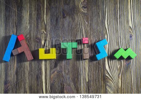 Word Autism built of wooden puzzles on a wooden background. Concept of autism word.