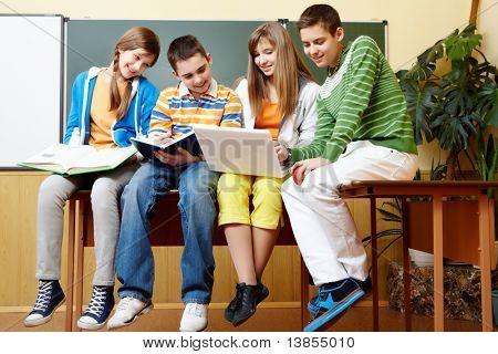 Retrato de inteligentes estudiantes sentados en el salón de clase y haciendo tareas escolares