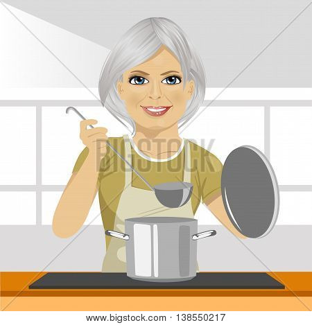 Smiling mature woman with a ladle cooking soup in pan at domestic kitchen