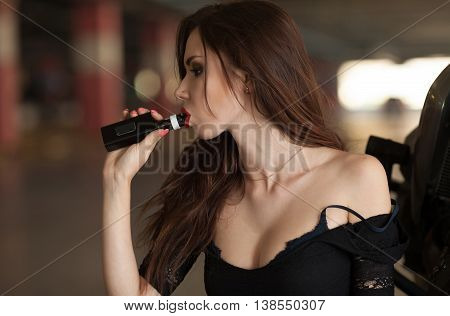 Elegant woman smoking e-cigarette with smoke portrait on bike