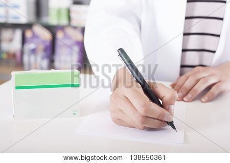 Pharmacist or doctor writing on tablet package with copy space