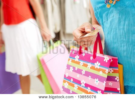 Image with focus on woman?s hand giving plastic card in the mall