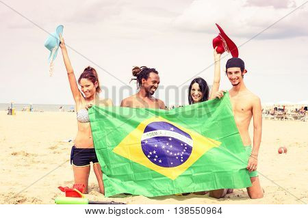 Group of cheerful friends holding brazilian flag at beach games party - Multiracial students having fun taking holiday photo on sand - Concept of joyful moment around the world - Soft vintage filter