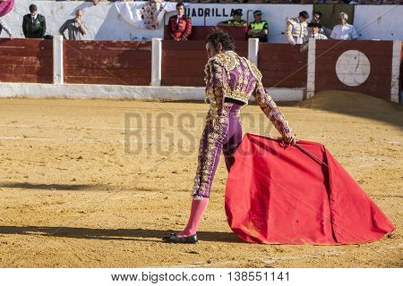 Andujar Jaen province SPAIN - September 12 2008: Spainish bullfighter Finito de Cordoba bullfighting with a crutch in a beautiful pass by low in the Bullring of Andujar Jaen province Andalusia Spain