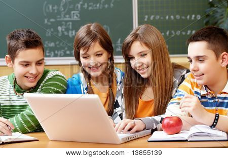 Portrait of clever students sitting at lesson and looking at laptop monitor