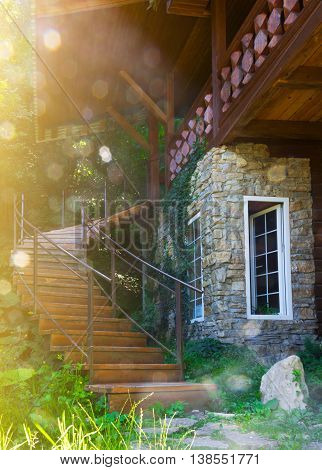 house of stone and wood with a spiral staircase in the sunlight. selective focus