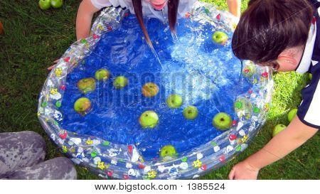 Girls Playing Apple Bobbing.Children Games