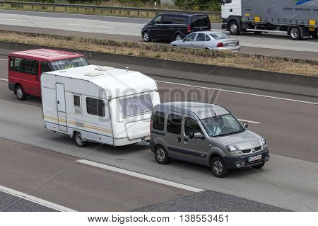FRANKFURT GERMANY - JULY 12 2016: Renault Kangoo 4x4 with a caravan driving on the highway in Germany