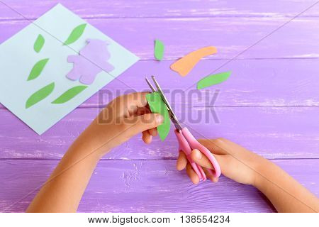 Child cuts a leaf from green paper. Kid holds scissors in his hands. Details to create a card. Child doing crafts from colored paper. Art project for kindergarten, summer camps