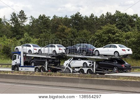 FRANKFURT GERMANY - JULY 12 2016: Car tranporter truck with new Mercedes Benz automobiles on the highway in Germany
