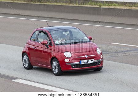 FRANKFURT GERMANY - JULY 12 2016: Red Fiat 500 driving on the highway in Germany