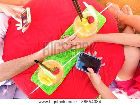 Friends hands holding phone table top view with fruit drinks - Couple using mobile scene from above at beach bar - Concept of people technology addiction in every situation
