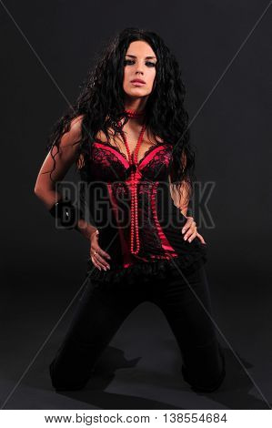 Sexy brunette in corset posing isolated on black