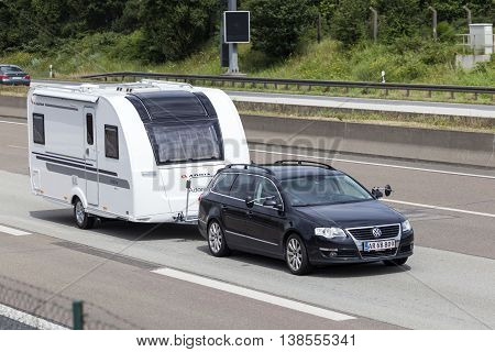 FRANKFURT GERMANY - JULY 12 2016: Volkswagen Passat Estate family car towing a caravan on the highway in Germany