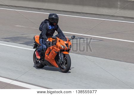 FRANKFURT GERMANY - JULY 12 2016: Motorcyclist on the orange Kawasaki Ninja ZX-6R motorcycle driving on the highway in Germany