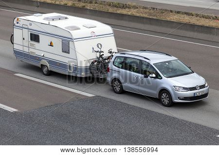 FRANKFURT GERMANY - JULY 12 2016: Volkswagen Sharan with a caravan driving on the highway in Germany