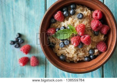 Food background with plate of oat flakes raspberries and blueberries on blue vintage board. Eating or vegetarian concept.