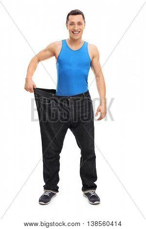 Full length portrait of a young handsome guy in a pair of oversized jeans isolated on white background
