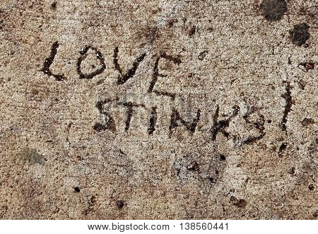 Cynical sentiment scratched into cement, love stinks