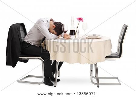Drunk and lonely guy sitting at a restaurant table with his head down isolated on white background
