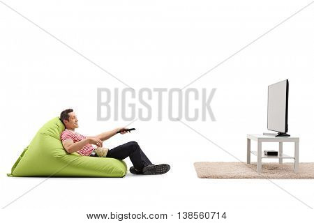 Relaxed man sitting on a comfortable green beanbag and watching TV isolated on white background