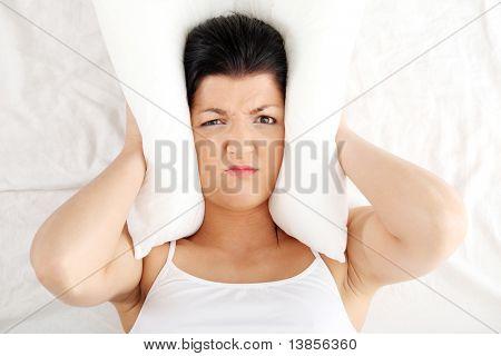 Vrouwelijke liggend op bed en haar oren met kussen sluiten.  Slapeloosheid