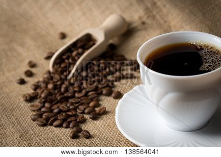 Cup of coffee with coffee beans and spice shovel on linen background front view closeup with copy space.