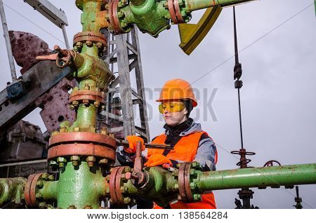 Woman engineer in the oil field repairing wellhead with the wrench wearing orange helmet and work clothes. Oil and gas concept.