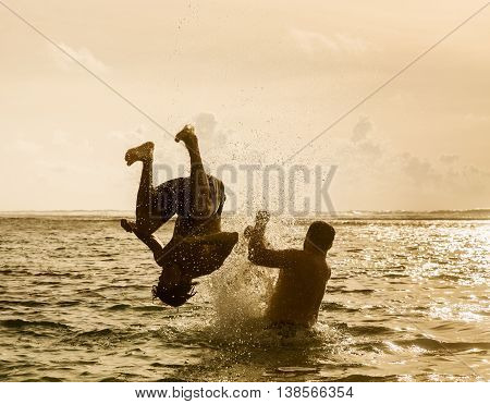 Silhouette of young man jumping out of the ocean which throws strong two man on the background of the expiring sunset