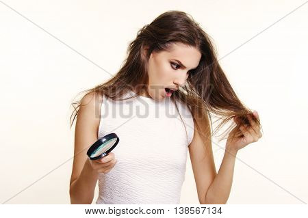 beautiful girl surprised and unhappy with her dry and damaged hair holding magnifier