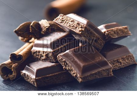 Two chocolate buildings on a dark background. energy and sugar. Broken bar. Chocolate blocks stack