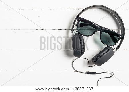 Sunglasses and headphones on white wooden desk