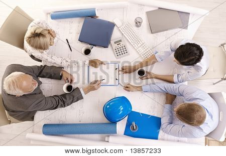 Businesspeople discussing work in office, sitting at meeting table, pointing at document, overhead view.?