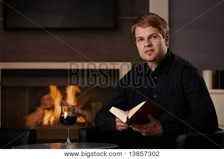 Young man sitting in front of fireplace at home on a cold winter day, reading book.?