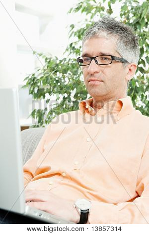 Mid-adult man wearing jeans and orange shirt sitting on couch, working with laptop computer. ?