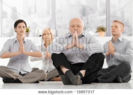 Business Team tun Yoga-Meditation, die formelle Kleidung, sitzen auf Boden mit Augen verschlossen