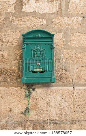 Postbox on brickwall. Giovinazzo. Puglia. Southern Italy.