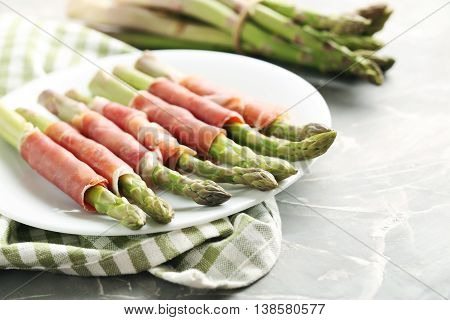 Fresh Green Asparagus Wrapped In Jamon On A Grey Table