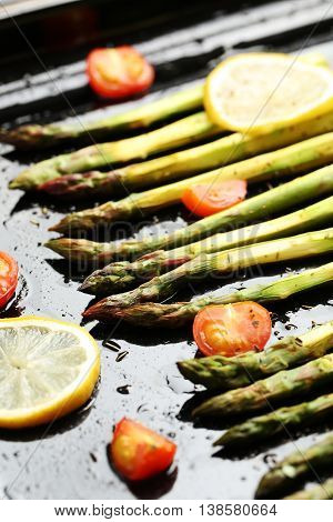 Fresh Baked Asparagus With Lemons And Tomatoes On Black Background