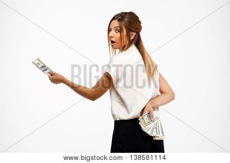 Portrait of young successful businesswoman winking, looking at camera, holding money over white background.
