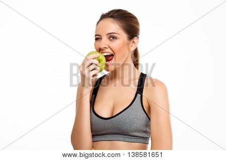 Portrait of young beautiful sportive girl smiling, winking, looking at camera, eating green apple over white background.