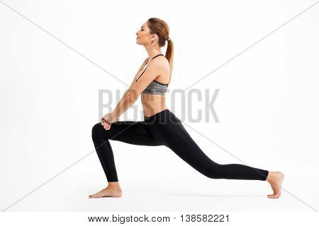 Portrait of young beautiful sportive girl smiling,  training over white background. Copy space.